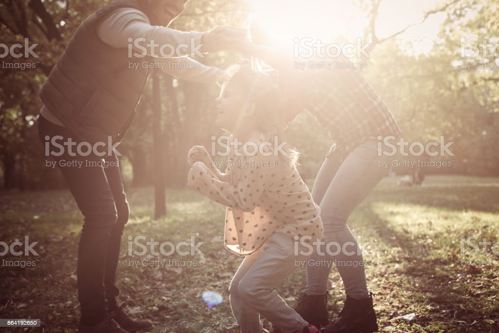 Cheerful parents with one child playing in nature together. royalty-free stock photo