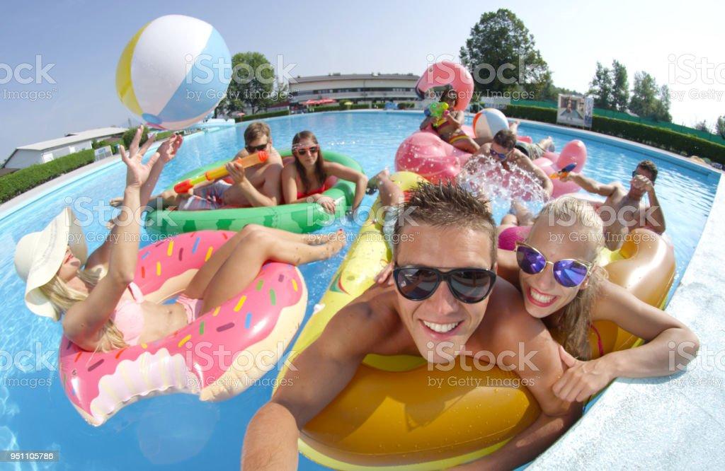 SELFIE: Cheerful people on fun colorful floaties having water gun fight in pool stock photo
