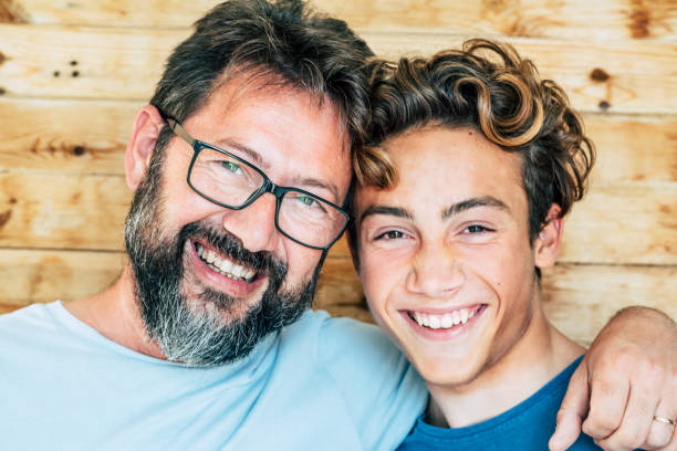 Cheerful people portrait with father and son hug and laughing a lot together having fun and looking at the camera - wooden background and joyful generations concept-handsome young and old males stock photo