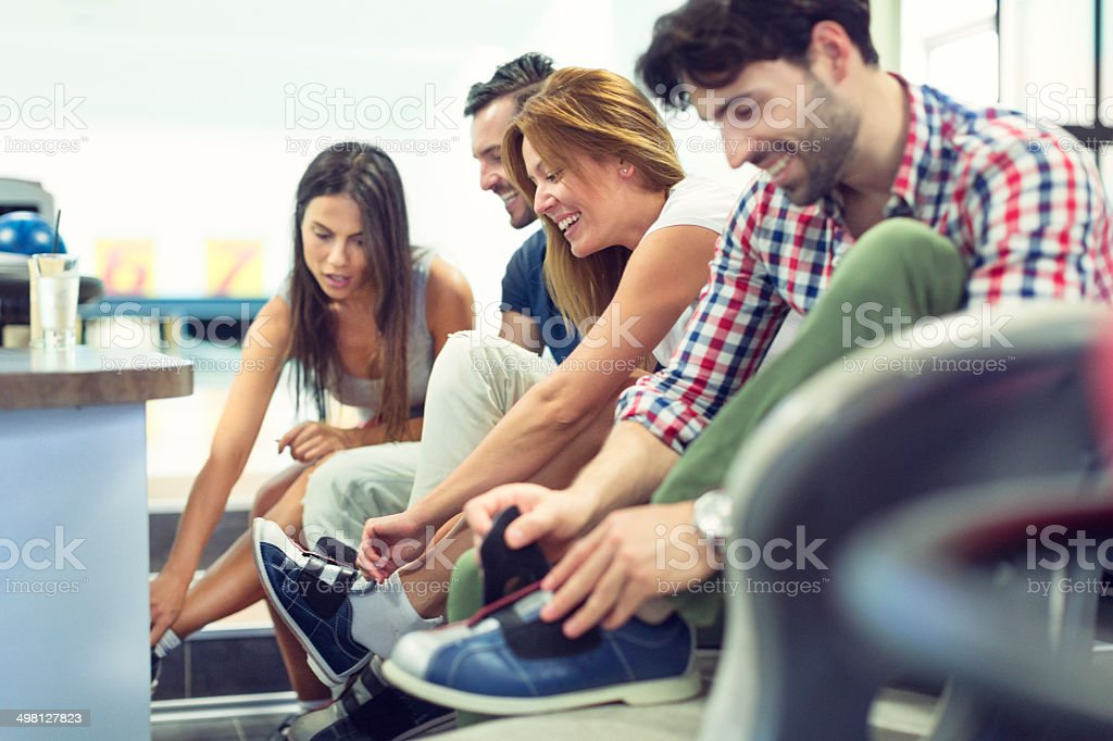 Cheerful People Putting On Bowling Shoes. stock photo