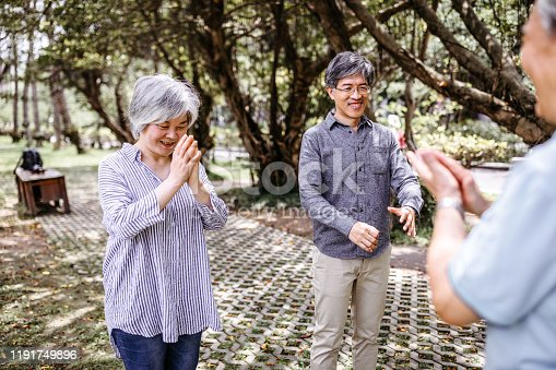 646614234 istock photo Cheerful people with teacher of Tai Chi outdoor 1191749896