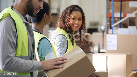 Attractive young mixed race woman talks with a female coworker while working in a distribution warehouse. They are preparing packages for delivery.