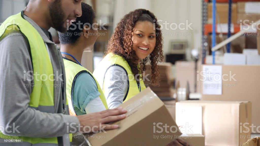 Cheerful people working in distribution warehouse stock photo