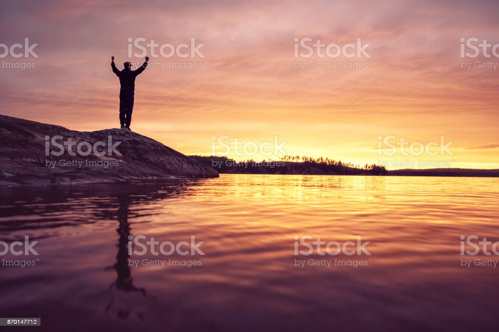 Man standing on a rock formation at a lake