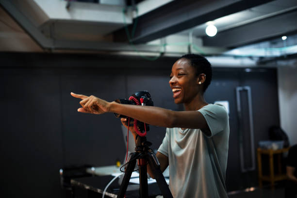 Cheerful photographer giving instructions in the studio Cheerful photographer giving instructions in the studio producer stock pictures, royalty-free photos & images