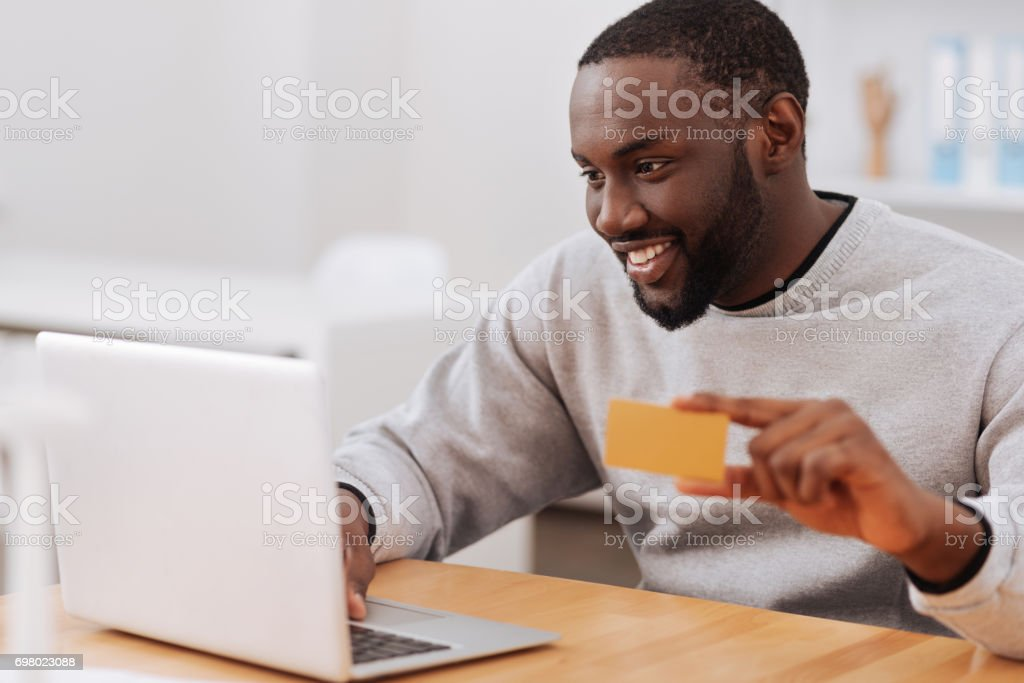 Cheerful pleasant man making an online payment stock photo