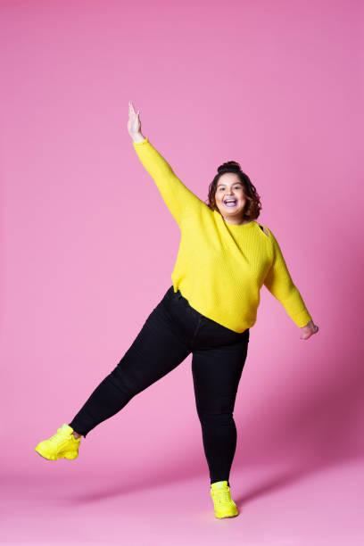 カジュアルな服装で陽気なプラスサイズモデル、ピンクの背景に黒いジーンズと黄色のジャンパーで太った女性 - real bodies ストックフォトと画像