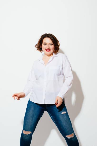 plus size frau tanzen fröhlich - damen jeans übergrößen stock-fotos und bilder