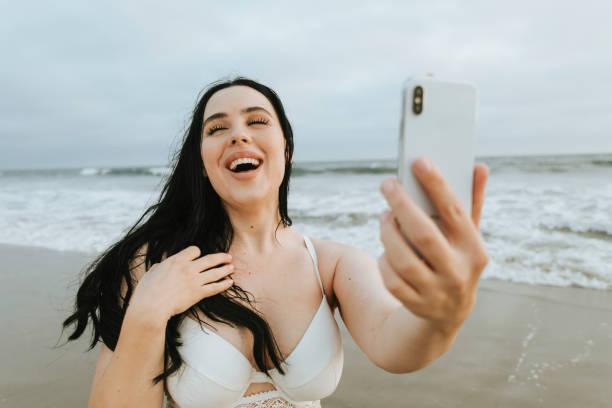ビーチで、selfie を取って陽気なプラスのサイズの女性 - real bodies ストックフォトと画像