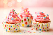 Homemade birthday party cupcakes with colorful polka dots.