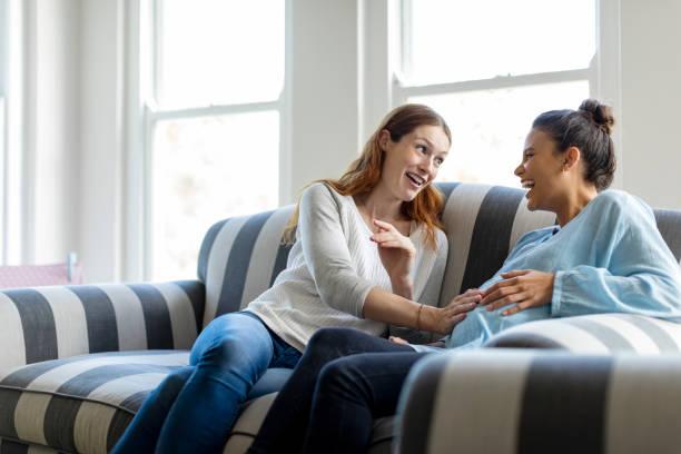 Mujer embarazada alegre hablar con amigo en casa - foto de stock
