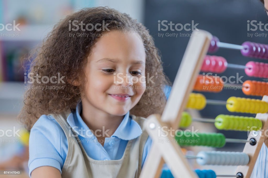 Mixed race preschool student smiles while using an abacus in her...