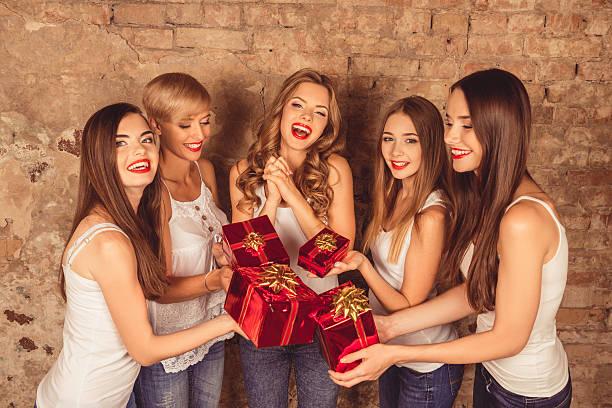 cheerful pretty girls giving presents to their friend - jugendliche geburtstag geschenke stock-fotos und bilder