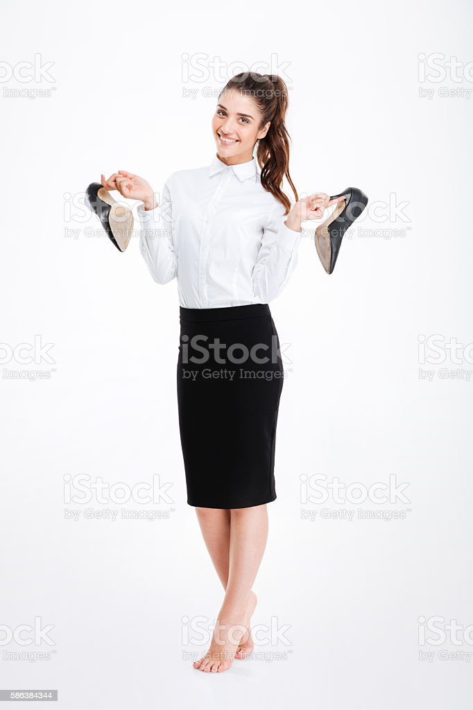 Cheerful pretty young businesswoman standing and holding high heels shoes стоковое фото