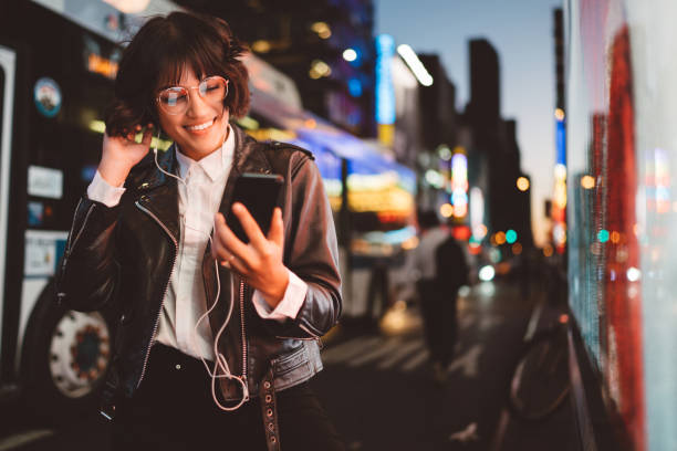 Cheerful pretty young woman in cool eyeglasses and trendy wear walking on metropolis street with night lights enjoying audio songs from playlist in earphones connected to smartphone device stock photo