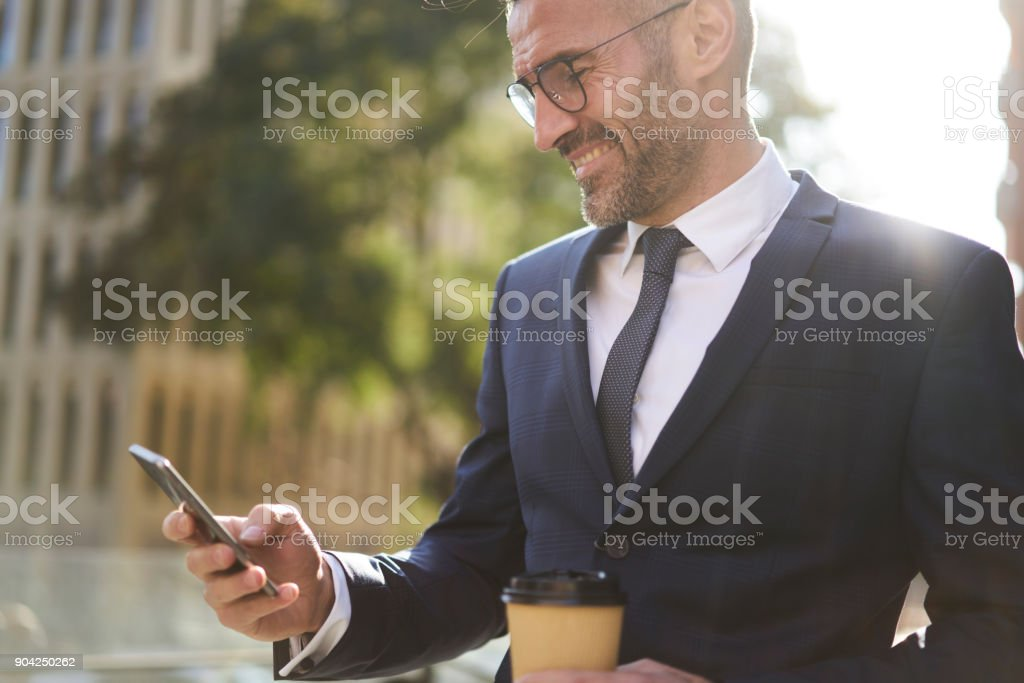 Cheerful professional experienced male editor of financial magazine monitoring work of journalist on internet reading latest publication on website satisfied by creative articles during break outdoors stock photo