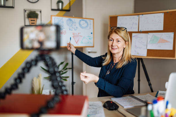 Cheerful professor communicate with pupils over video call Mature smart professor holding online class for e-learning school kids and students desolation stock pictures, royalty-free photos & images