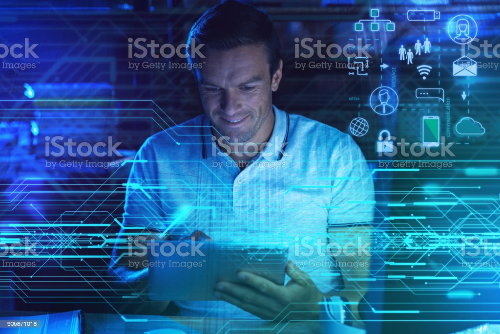 Cheerful programmer smiling while holding his new amazing device stock photo