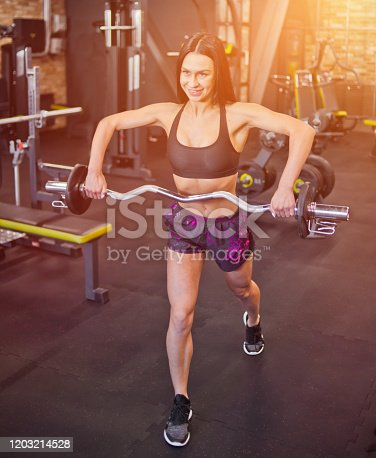 Cheerful purposeful brunette athlete doing exercise with barbell in the hands of the gym.