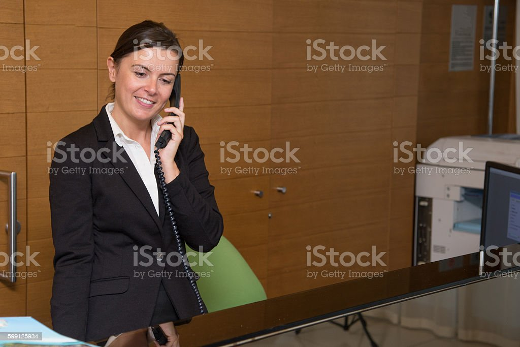 Cheerful receptionist answering at the telephone stock photo