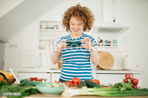 A curly red hair female using her smart phone to record a vlog for her channel concerning food and healthy lifestyle