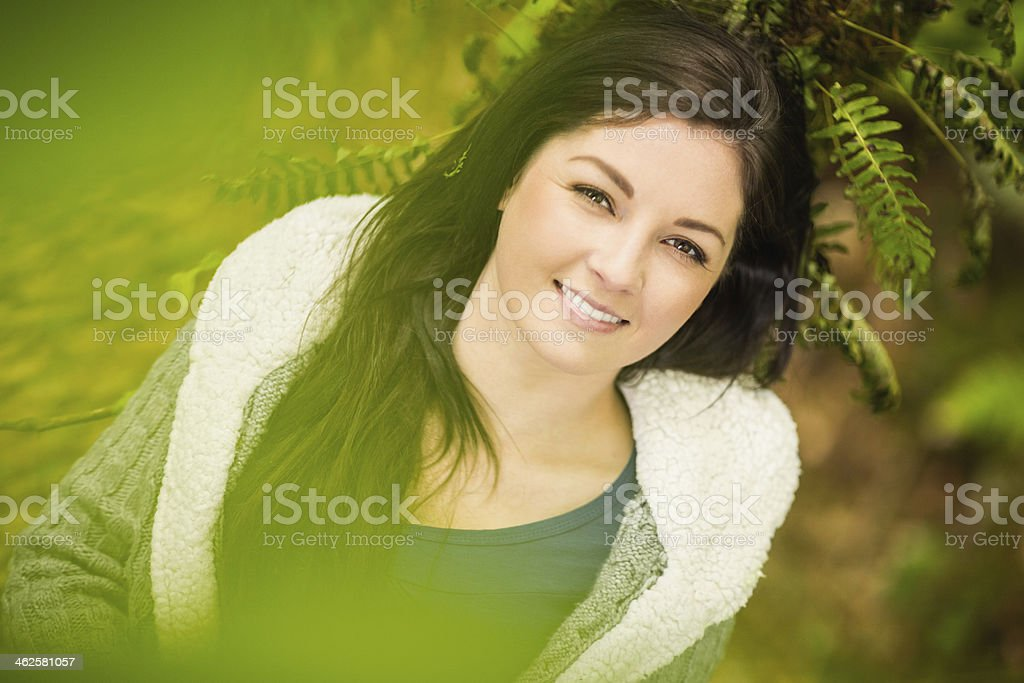 Cheerful relaxed woman lying on a branch royalty-free stock photo