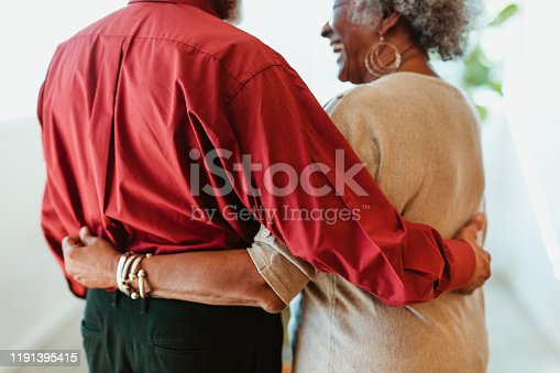 Rear view of cheerful retired couple standing at home. Midsection of senior man and woman are with arms around. They are spending leisure time together.