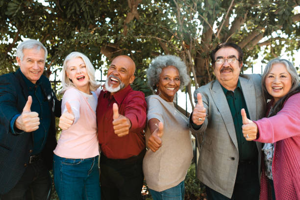 Cheerful retired senior friends showing thumbs up stock photo