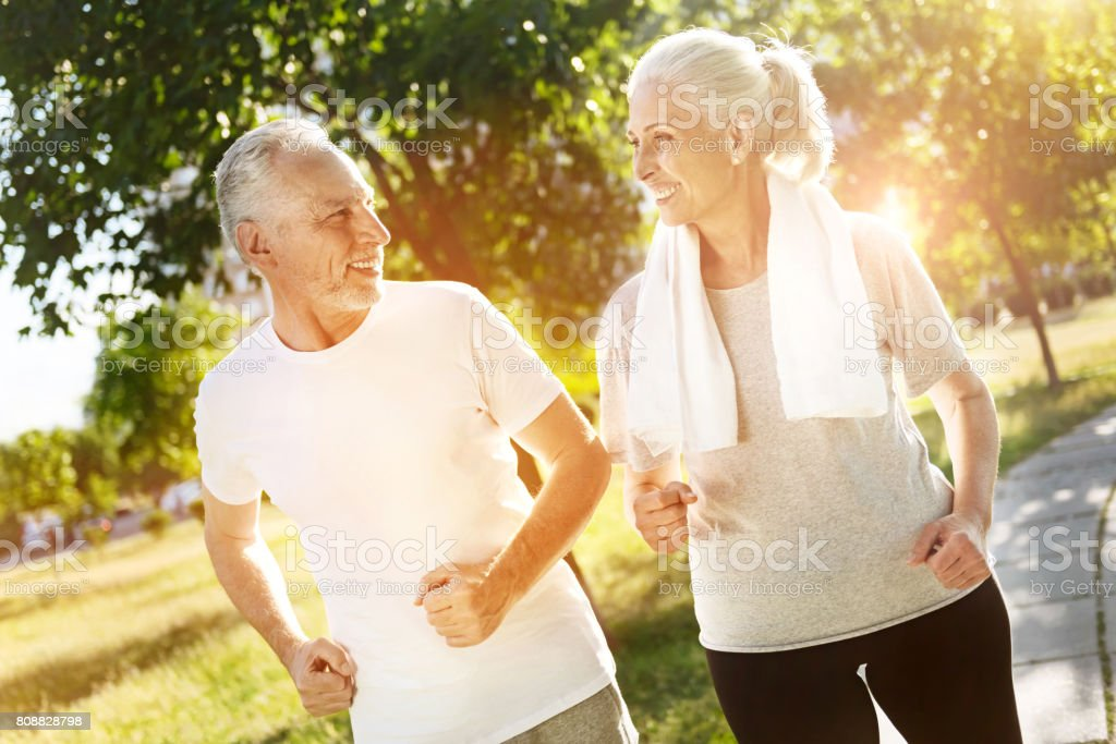 Cheerful retired smiling couple jogging together stock photo