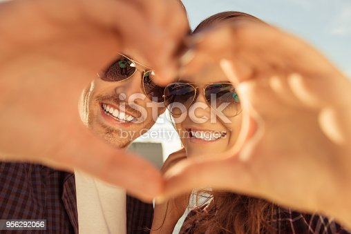 950598260 istock photo Cheerful romantic couple making heart gesture with hands 956292056