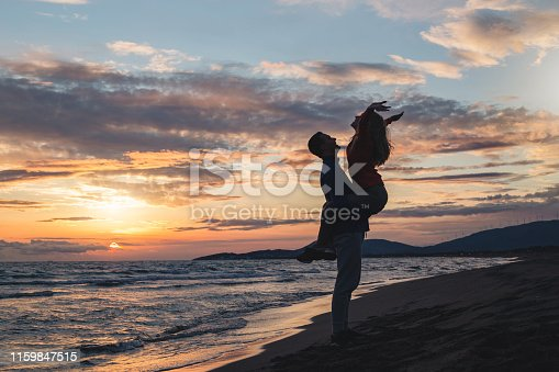 926982852 istock photo Cheerful romantic couple on the beach during sunset 1159847515