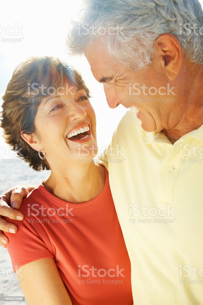 Cheerful romantic mature man and woman enjoying on the beach royalty-free stock photo