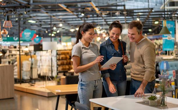 vrolijke verkoop vrouw die een ontwerp toont op tablet tot mid adult couple op zoek naar meubels in een thuiswinkel - showroom stockfoto's en -beelden