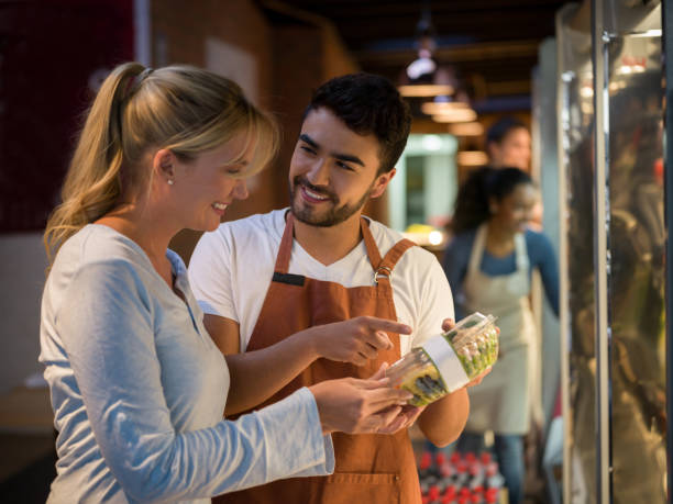 Cheerful salesman suggesting a new salad to a beautiful customer both smiling Cheerful salesman suggesting a new salad to a beautiful customer both smiling while the rest of the team work putting products in the refrigerator salesman stock pictures, royalty-free photos & images