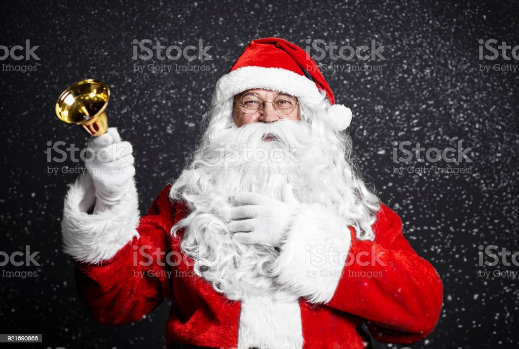 Cheerful santa claus holding handbell stock photo