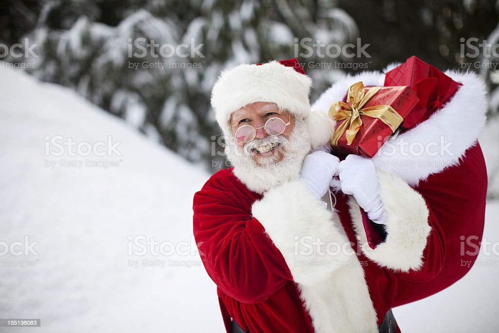 Cheerful Santa Claus Walking in Winter Snow with Christmas Gifts royalty-free stock photo