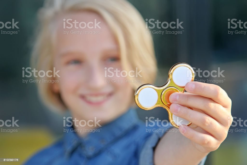 Cheerful school aged girl playing with a gold fidget spinner. A popular trendy toy. stock photo