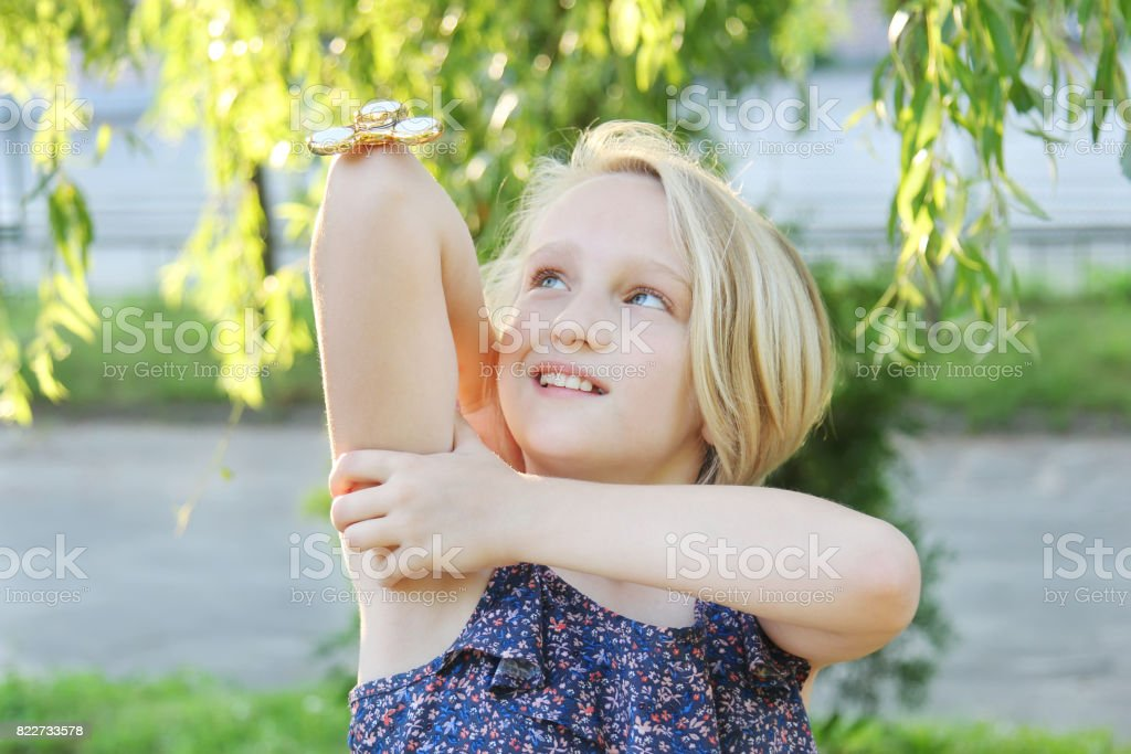 Cheerful school aged girl playing with a gold fidget spinner. A popular trendy toy spinning on the elbow. stock photo