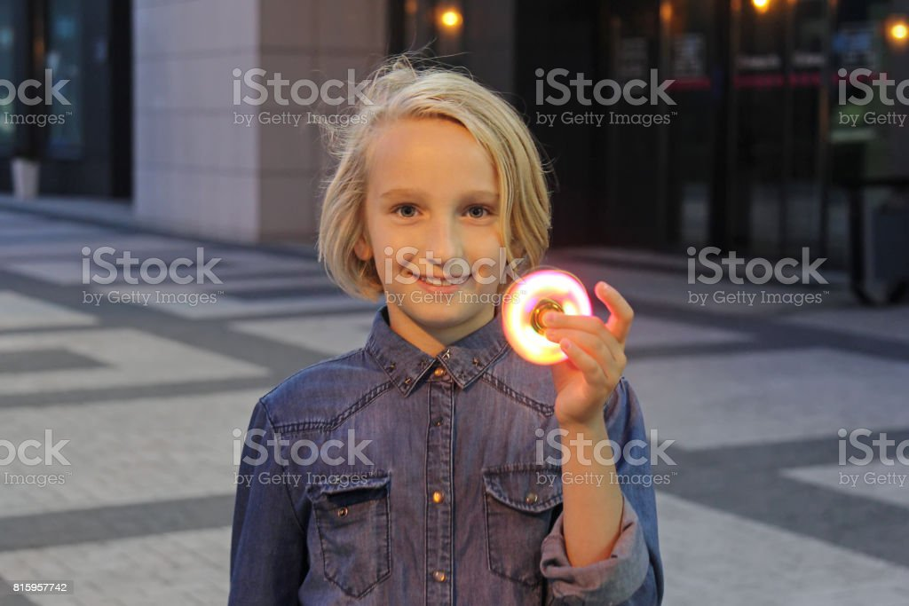 Cheerful school girl playing with a luminous fidget spinner, evening outdoors. A popular trendy toy. stock photo