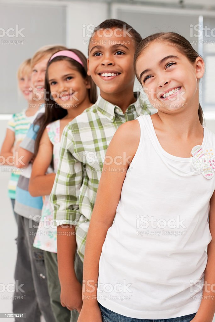 Cheerful school kids standing in a line royalty-free stock photo