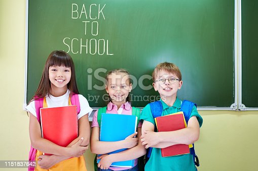 Smiling boy and girls with backpacks and notepads standing against blackboard saying Back to school