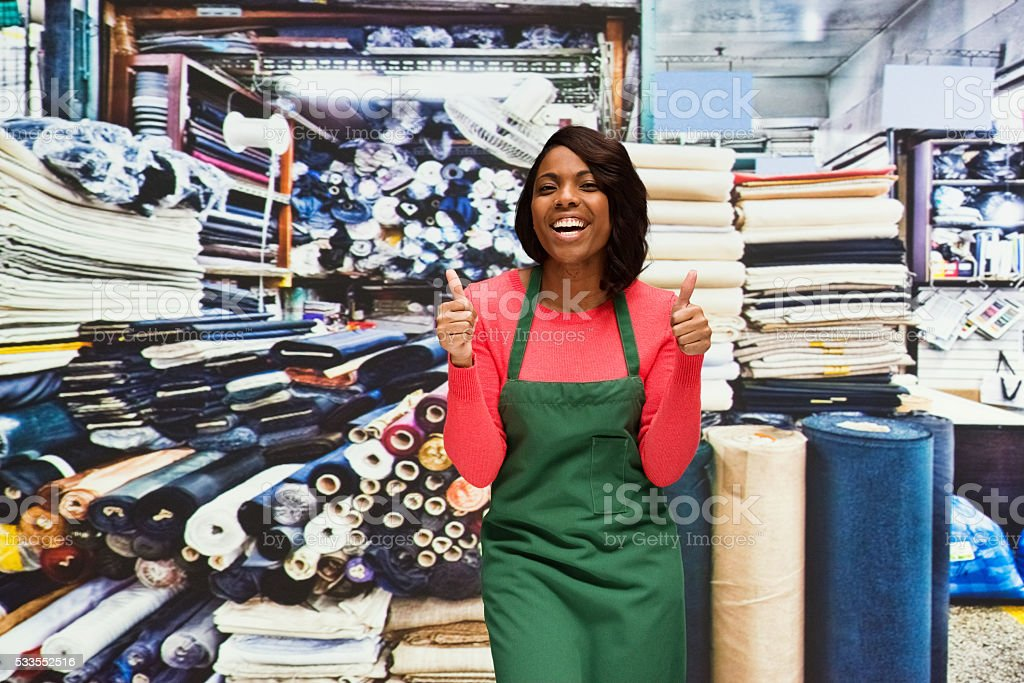 Cheerful seamstress showing thumbs up stock photo