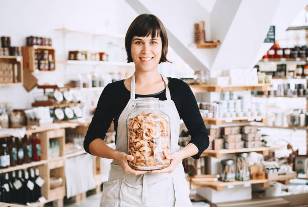 Cheerful seller assistant holding glass jar with groceries in plastic free store. stock photo