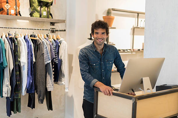 Cheerful seller man in clothing store. Working on computer stock photo