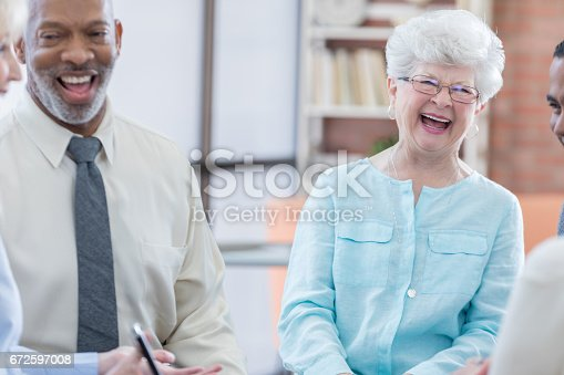 487670635istockphoto Cheerful senior adults in group therapy session 672597008