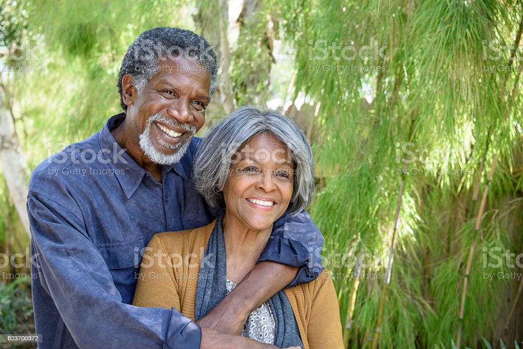 Cheerful senior African American couple in garden, smiling stock photo