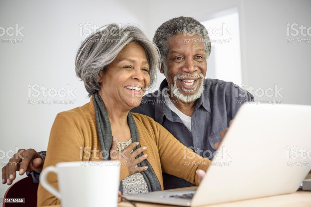 Cheerful Senior African American couple using laptop, smiling stock photo