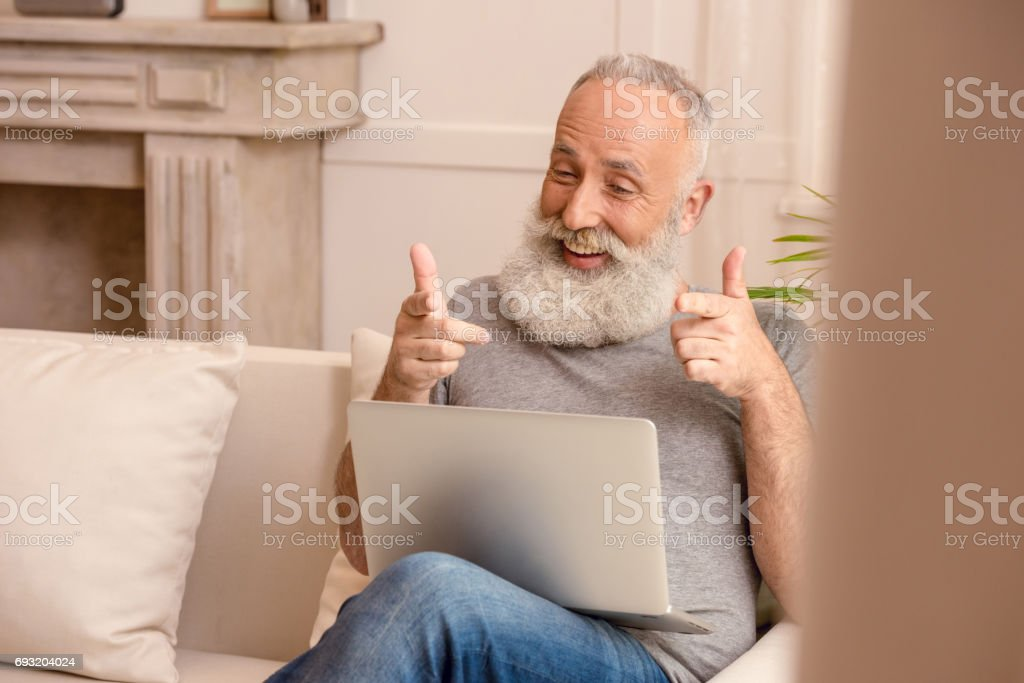 cheerful senior bearded man looking at laptop and pointing while sitting on sofa at home stock photo