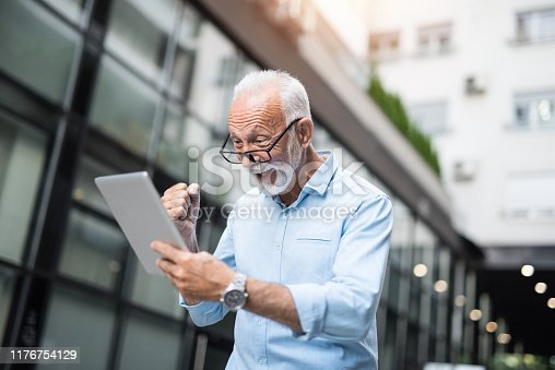 Cheerful senior businessman seeing great results on a digital tablet.