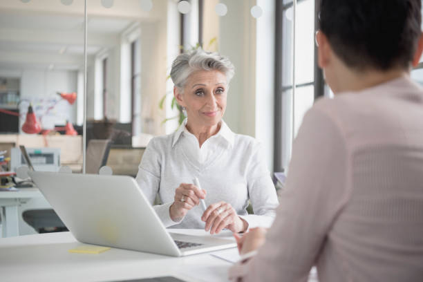 Cheerful senior businesswoman with laptop talking to colleague stock photo
